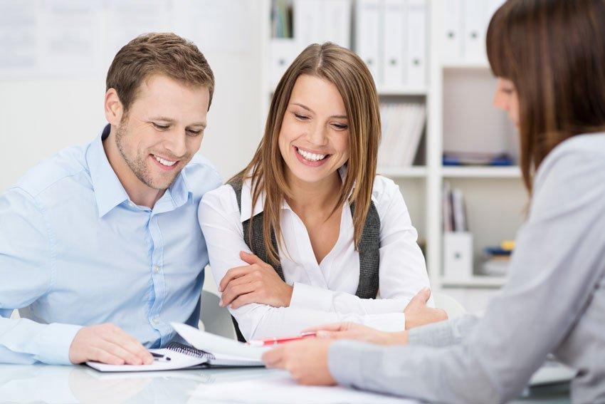 Пара изучает детали сделки во время консультации с банковским сотрудником