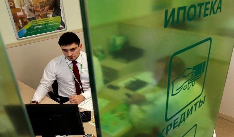 Сотрудник банка за стеклянной ширмой