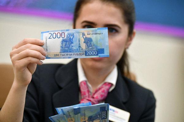 Девушка держит купюру 2000 рублей