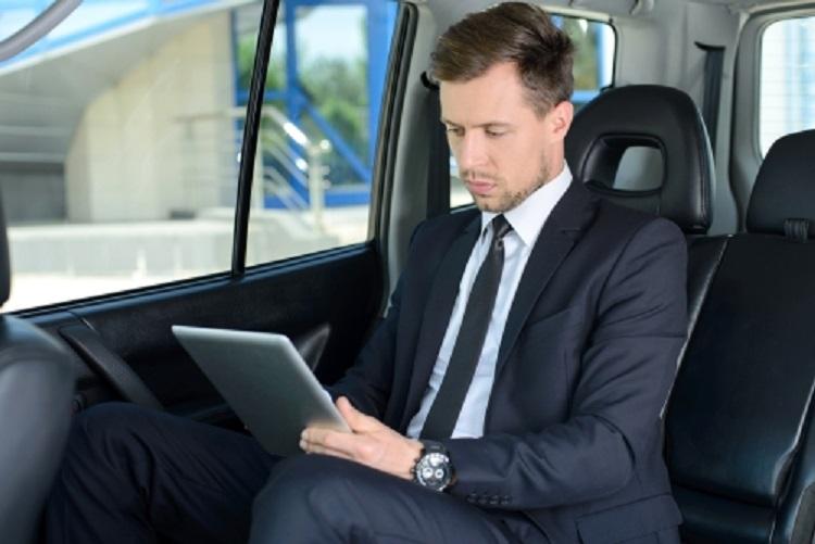 Деловой мужчина в машине с ноутбуком