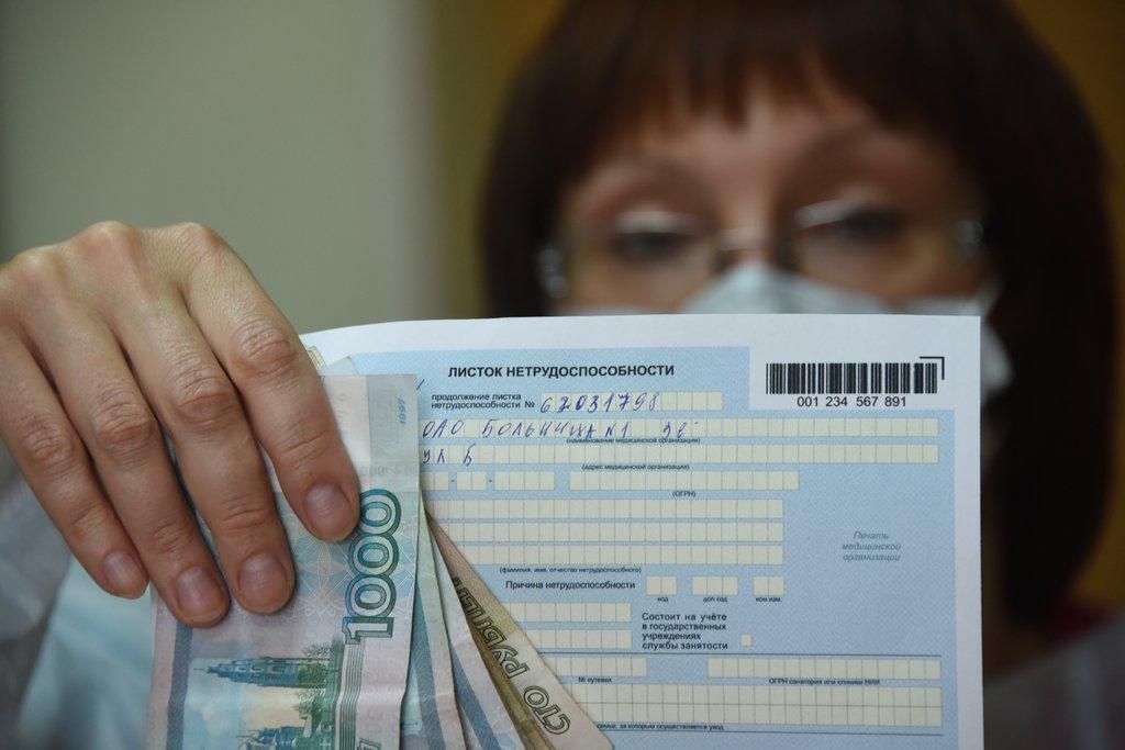 Женщина в маске и в очках держит в руке больничный лист и рубли