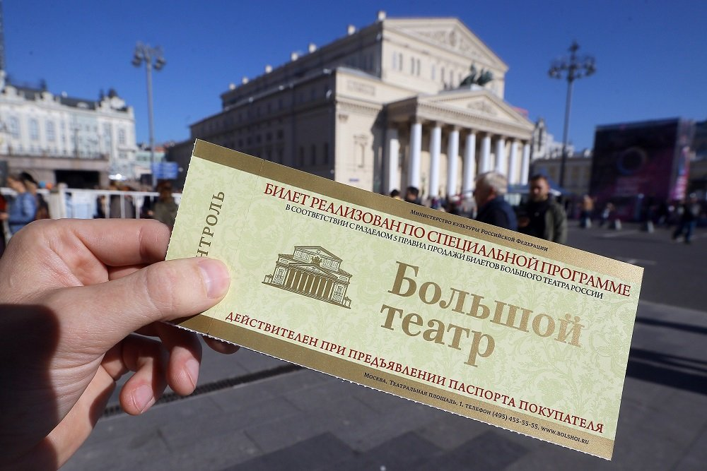 Билет в Большой театр в руке на фоне театра