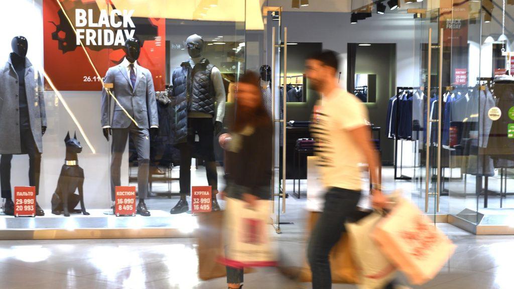 Люди с пакетами в магазине одежды