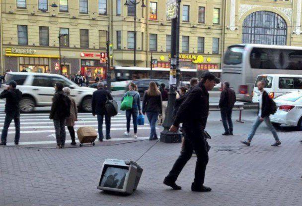 Человек тащит телевизор на веревке