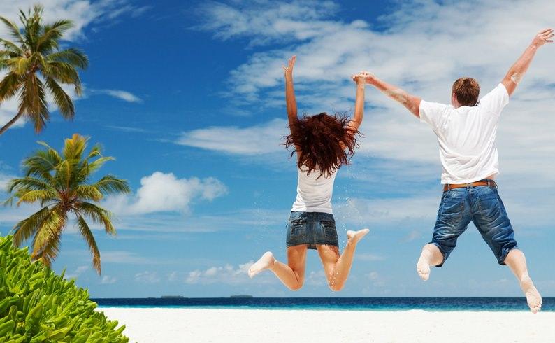 Девушка и парень в прыжке на пляже