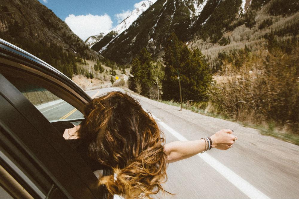 Девушка высуналась из окна в авто в горах