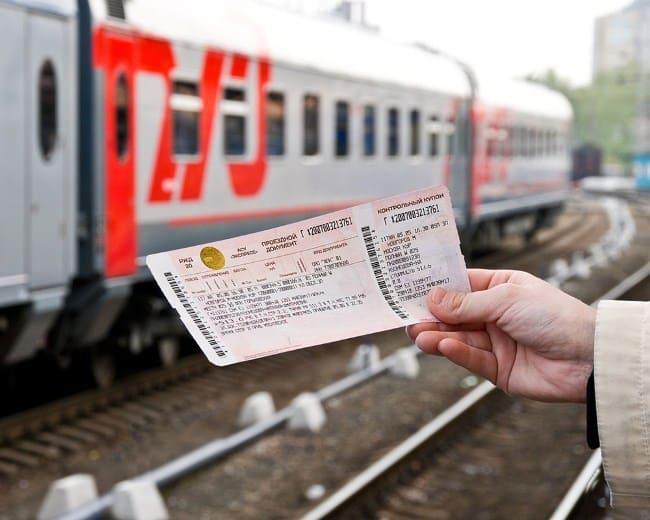 Железнодорожный билет в руках пассажира на фоне состава