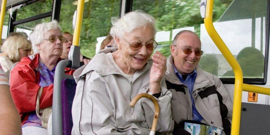 Пожилые люди смеются в автобусе