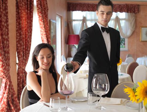 Официант наливает вино девушке