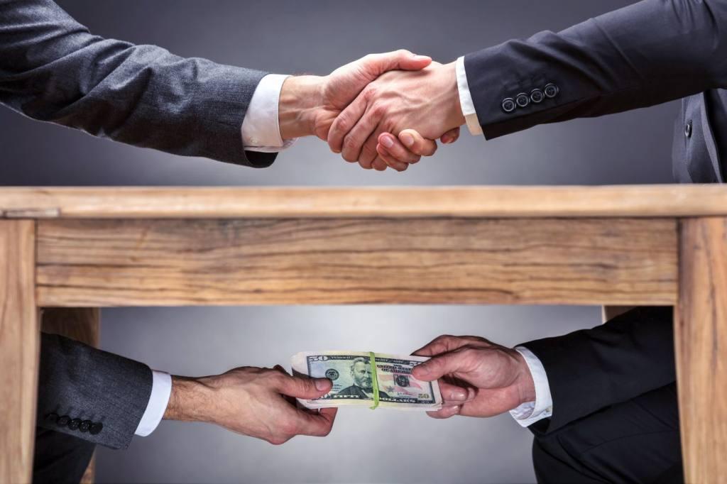 Пожатие руки и пачка денег под столом