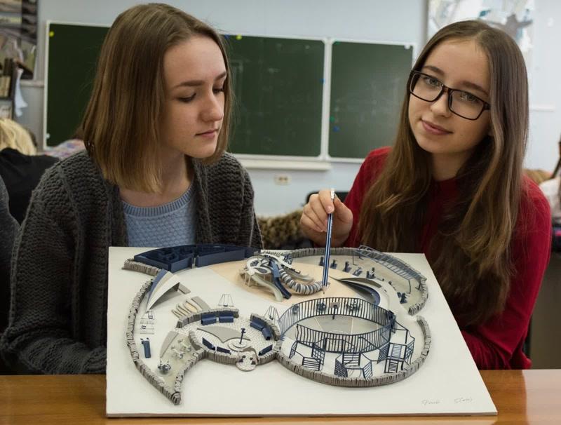 Девушки-студентки на практическом занятии держат в руках трехмерную модель сооружения