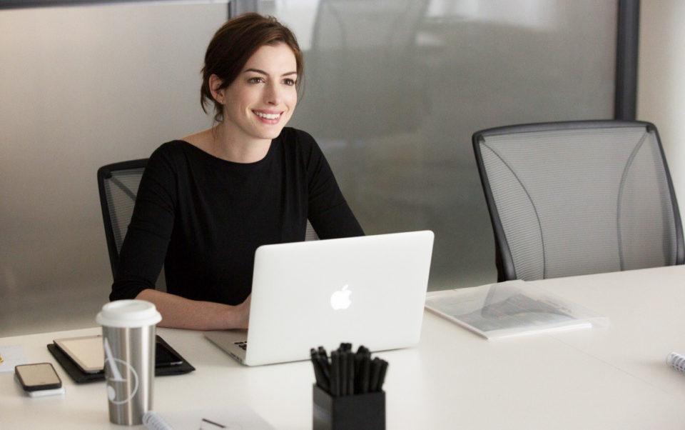 Девушка сидит за столом с ноутбуком и улыбается