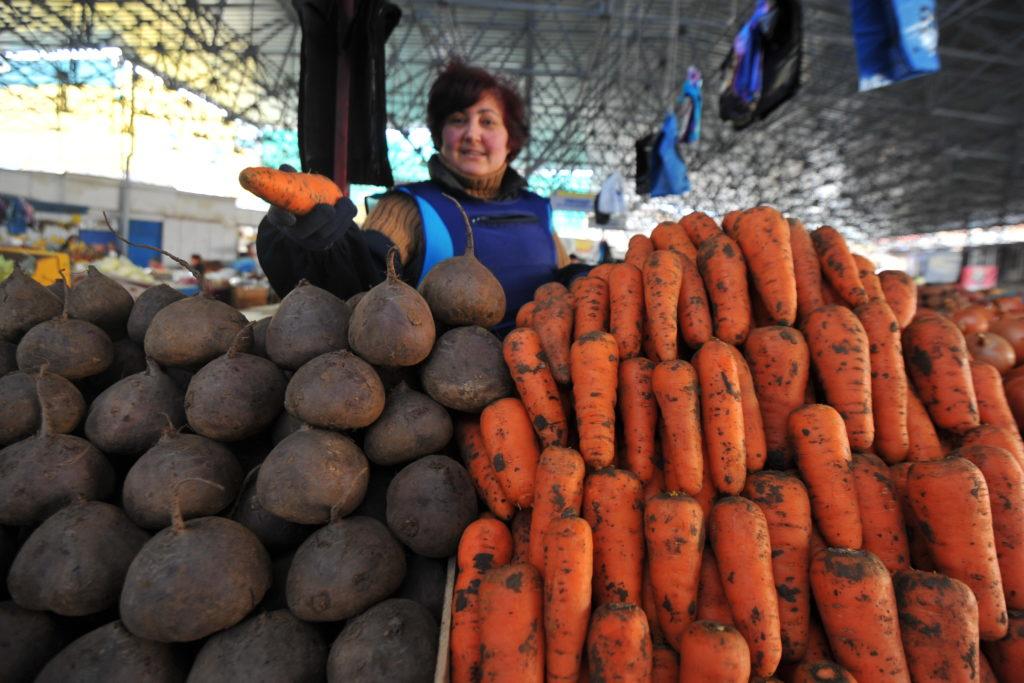 Женщина берет морковь в магазине