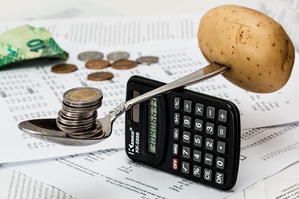 Произвольные весы из водруженной на калькулятор ложки с монетами и насаженной картошкой