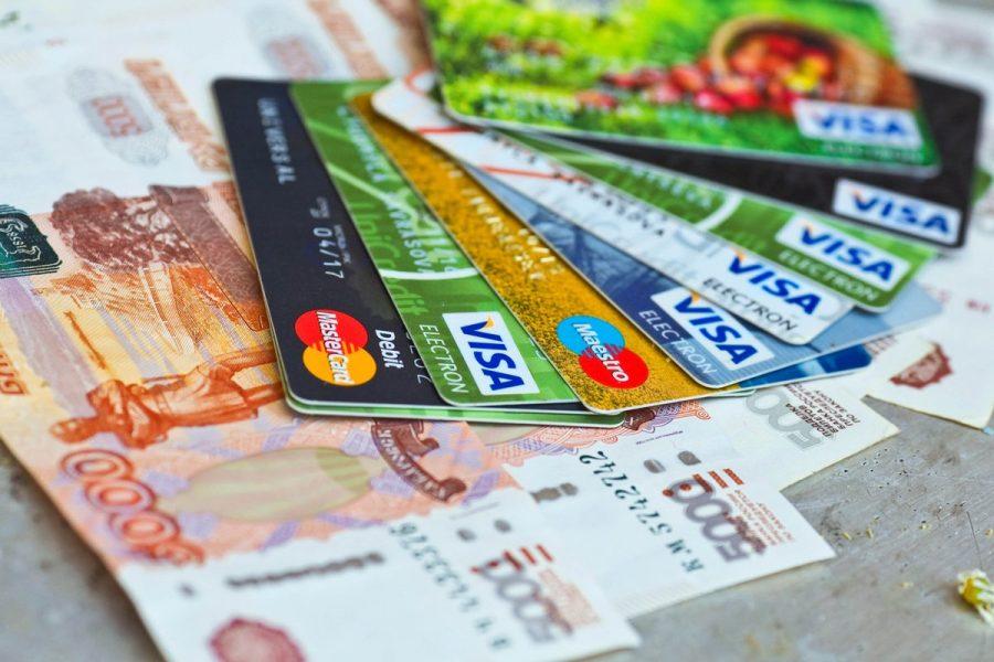 5-тысячные рублевые купюры и разложенный поверх них веер из банковских карт VISA