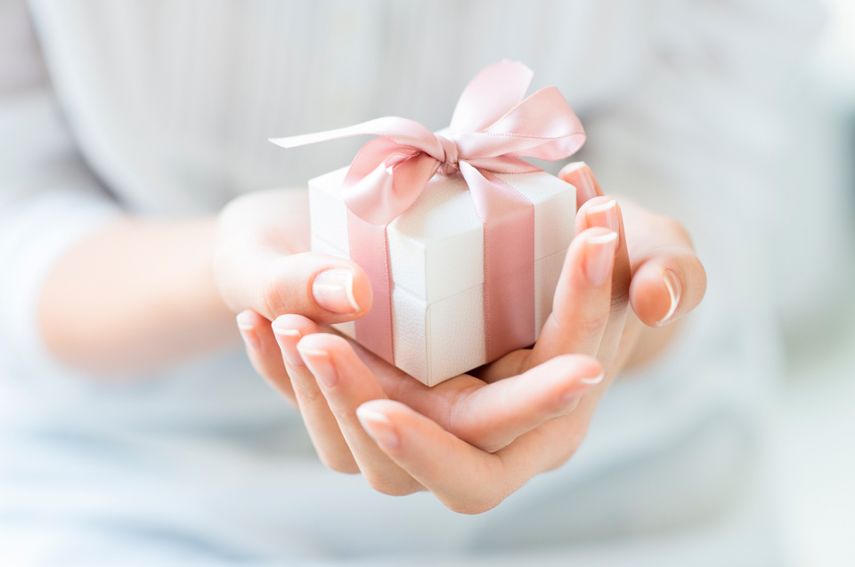 Подарок с шелковой лентой в женских руках