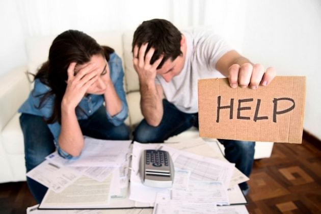 Молодая пара обхватила голову руками над счетами и табличка HELP в руках парня