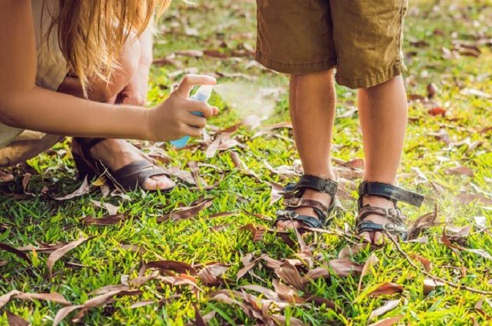 Нанесение спрея от комаров на ноги