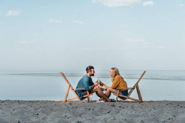 Парень и девушка на берегу на креслах