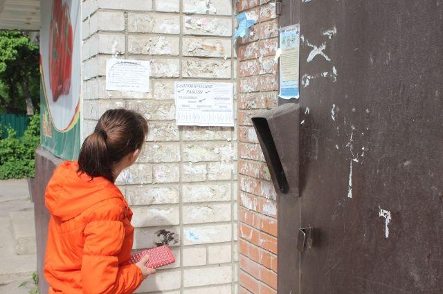 Женщина смотрит объявления о трудоустройстве на стене панельного дома