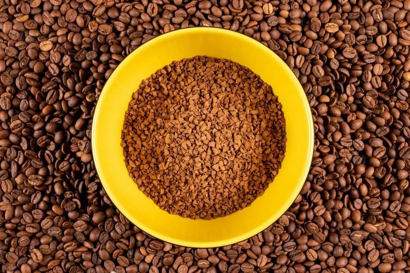 Растворимый кофе в пиале и зерна вокруг