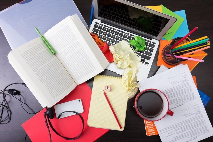 На столе чашка с чаем, книга, ноубук, карандажи и бумага