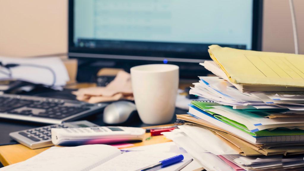 На столе чашка, компьютер, бумаги