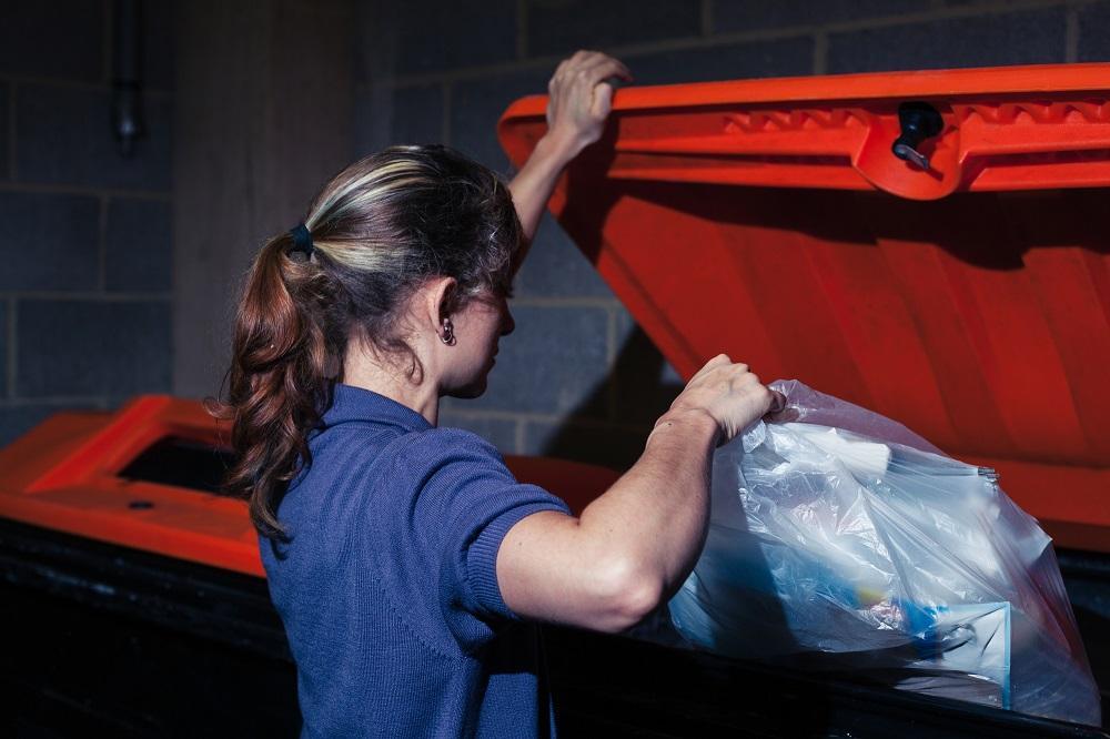 Девушка выбрасывает мусор в контейнер