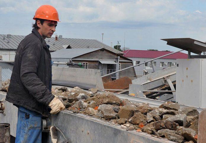 Молодой мужчина в строительной каске возле груды колотого кирпича