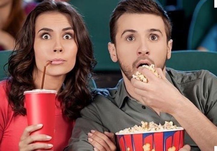 Люди в кинотеатре с попкорном и напитком
