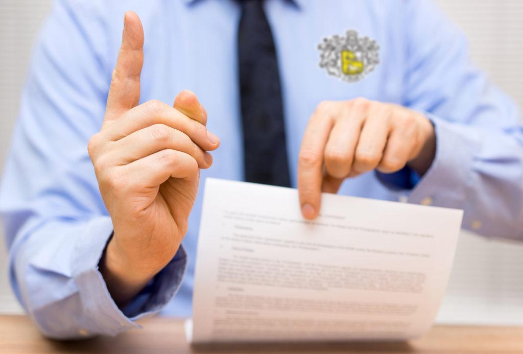 Банковский сотрудник с поднятым указательным пальцем и листком бумаги