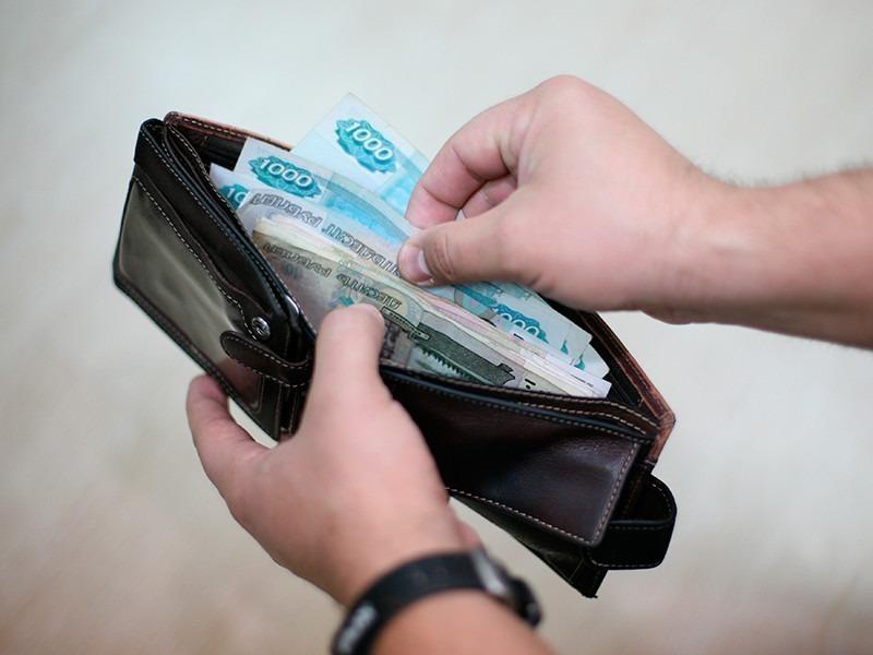 Кошелек с деньгами в мужских руках