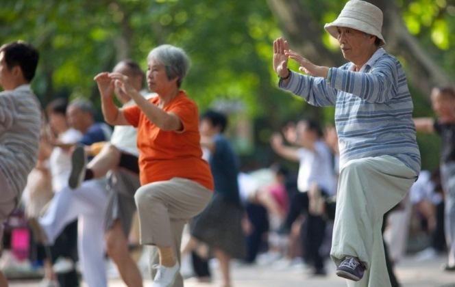 Пожилые китайцы делают цигун в парке
