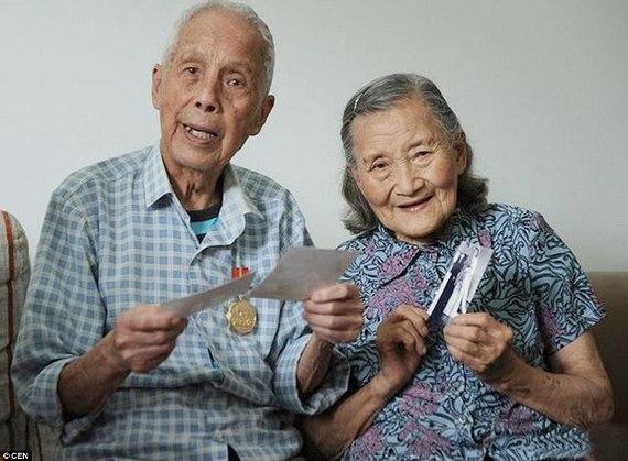 Пожилая китайская пара с фотографиями в руке