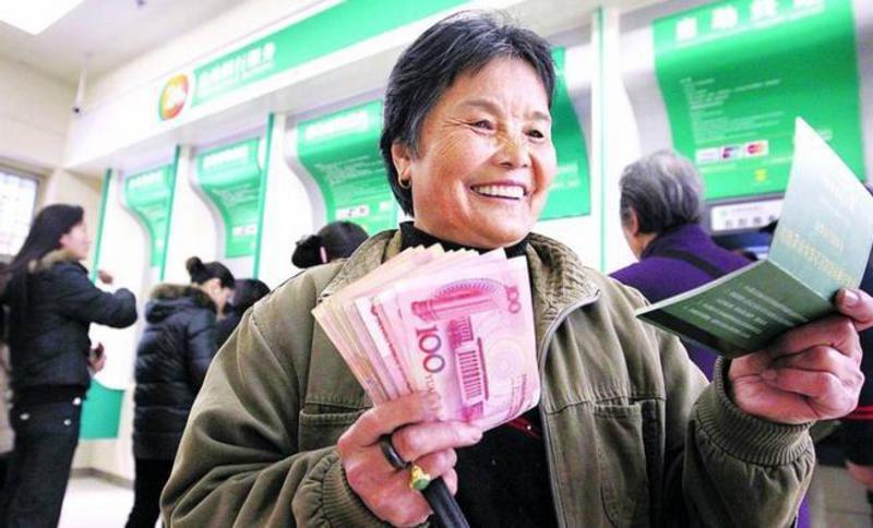 Китаянка в банке улыбается, держа стопку юаней в руке