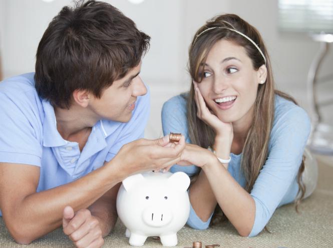 Молодая пара спорит возле копилки с монетами