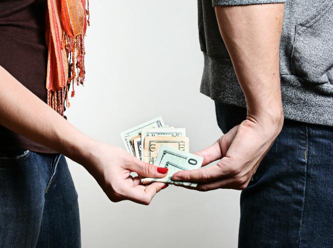 Мужчина передает сзади стоящей женщине доллары