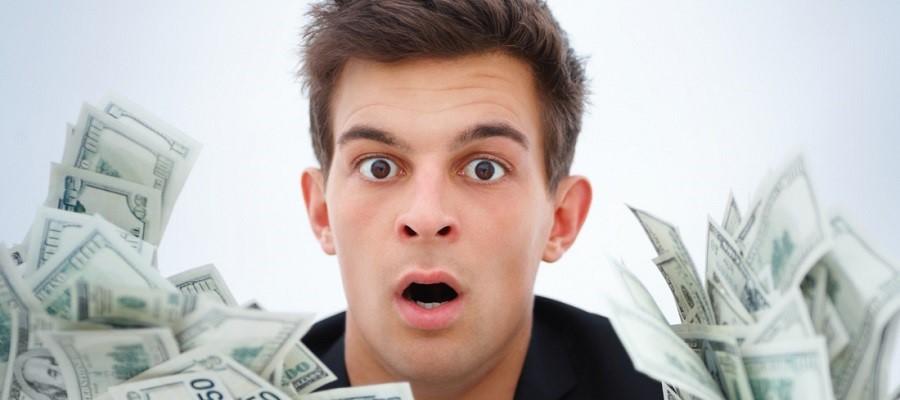 Удивленный парень с долларами в руках