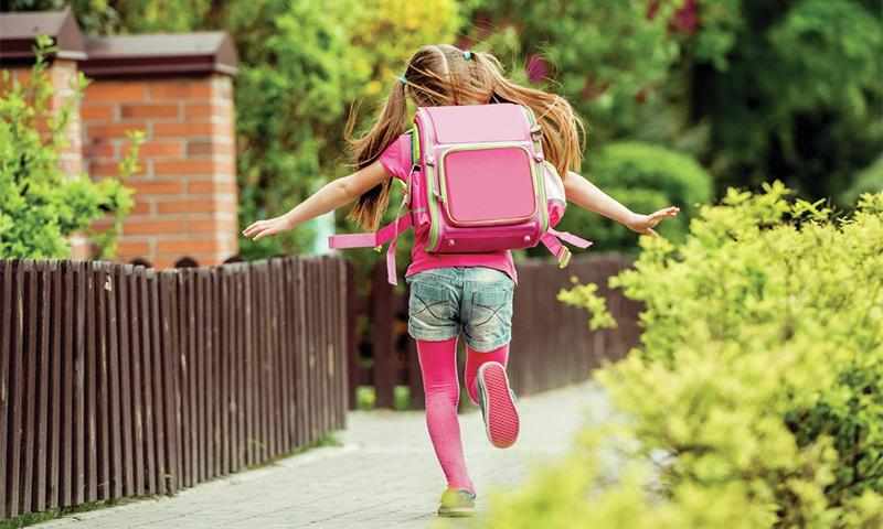 Маленькая девочка бежит после школа домой с рюкзаклм