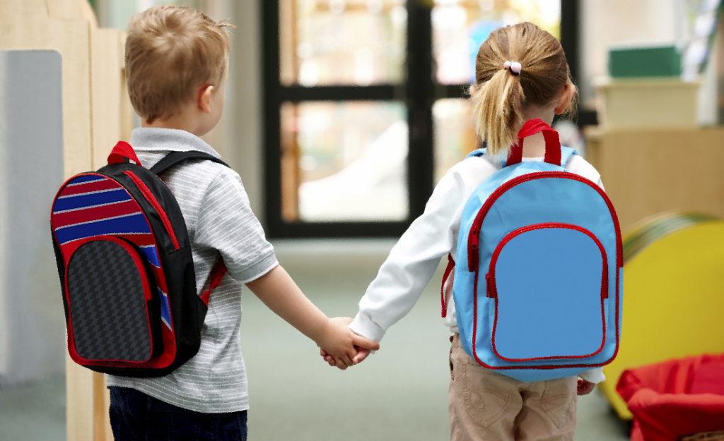 Маленький мальчик и девочка с ранцами за плечами держатся за руки