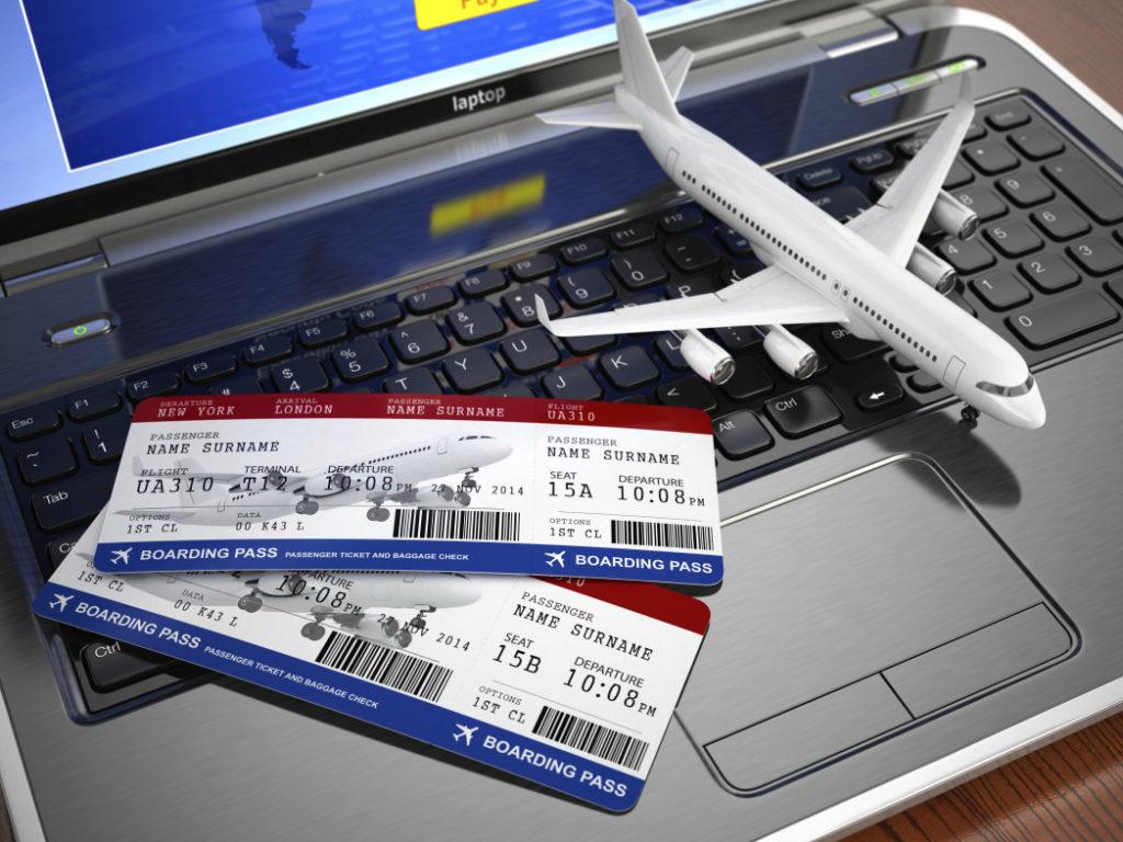 Игрушечный самолетик и авиабилеты на клавиатуре ноутбука