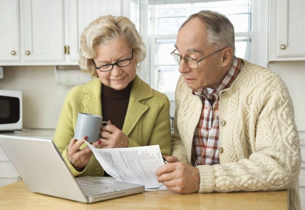 Два пенсионера читают документ