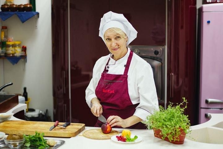 Женщина среднего возраста в поварском колпаке и фартуке на кухне