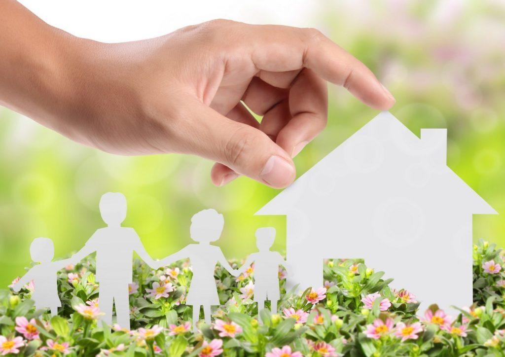 Рука трогает крышу картонного домика с семьей