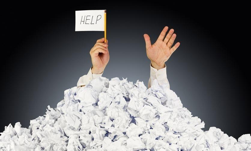 """Руки, торчащие из горы бумажных свертков с белым флагом и надписью """"HELP"""""""
