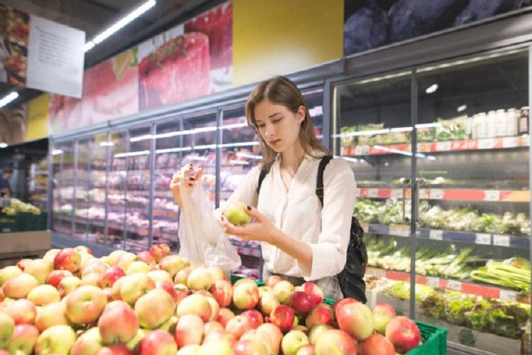 Девушка в магазине выбирает яблоки