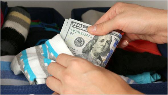 Человек прячет доллары в носок