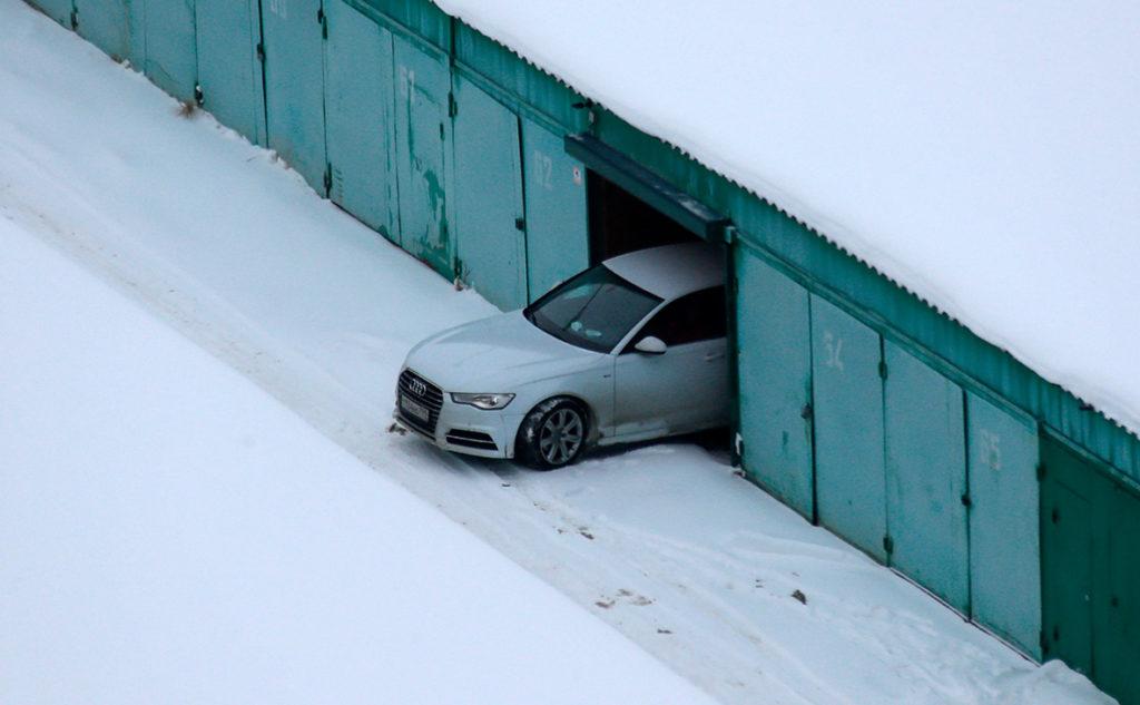 Машина выезжает из гаража в снег