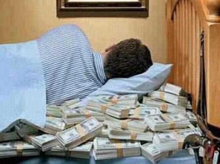 Человек спит на пачках денег