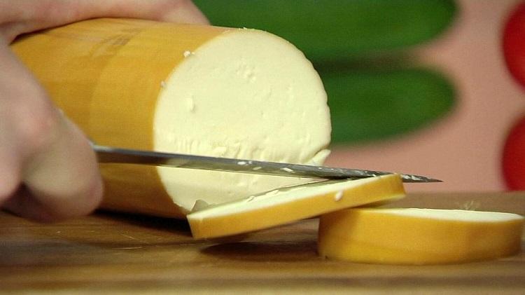 Человек режет колбасный сыр
